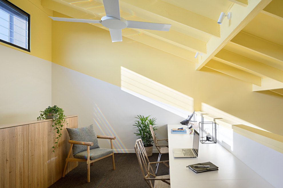 Design ideas for a contemporary home office in Geelong with yellow walls, carpet, a built-in desk and grey floor.