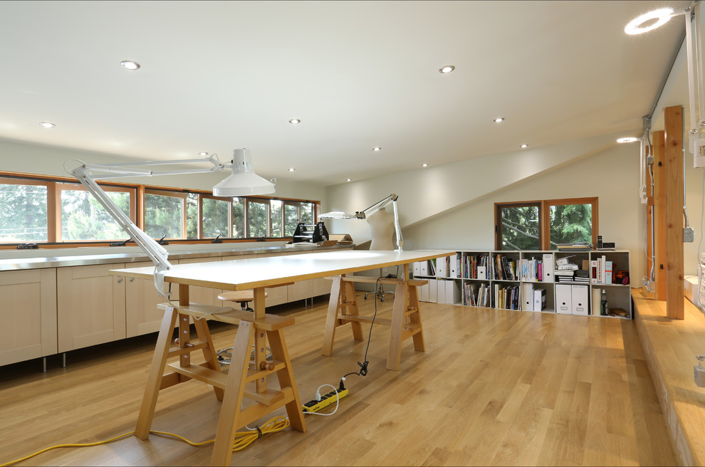 Example of a trendy freestanding desk light wood floor home studio design in Portland with white walls