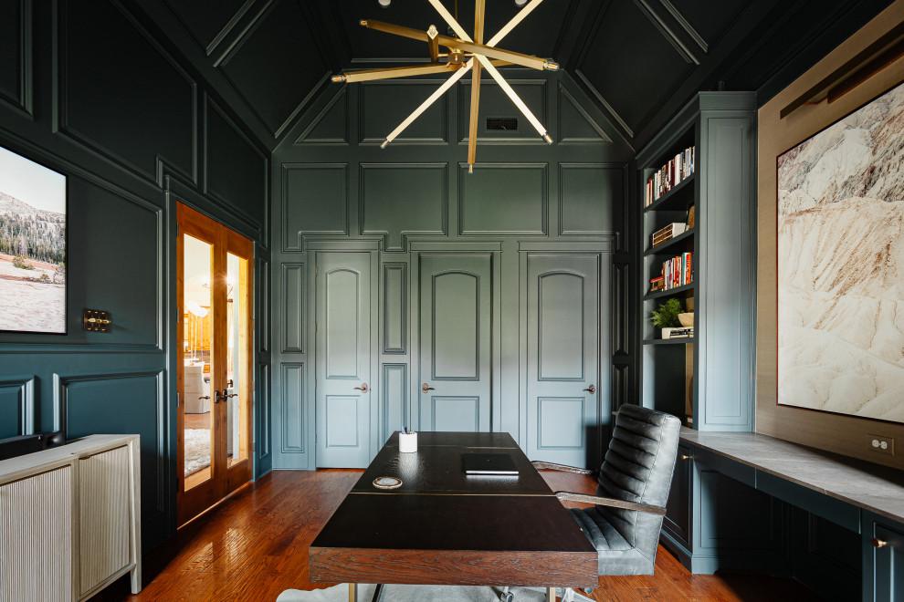 Ejemplo de despacho abovedado, clásico renovado, de tamaño medio, con paredes verdes, suelo de madera en tonos medios, todas las chimeneas, marco de chimenea de piedra, escritorio independiente, suelo marrón y panelado