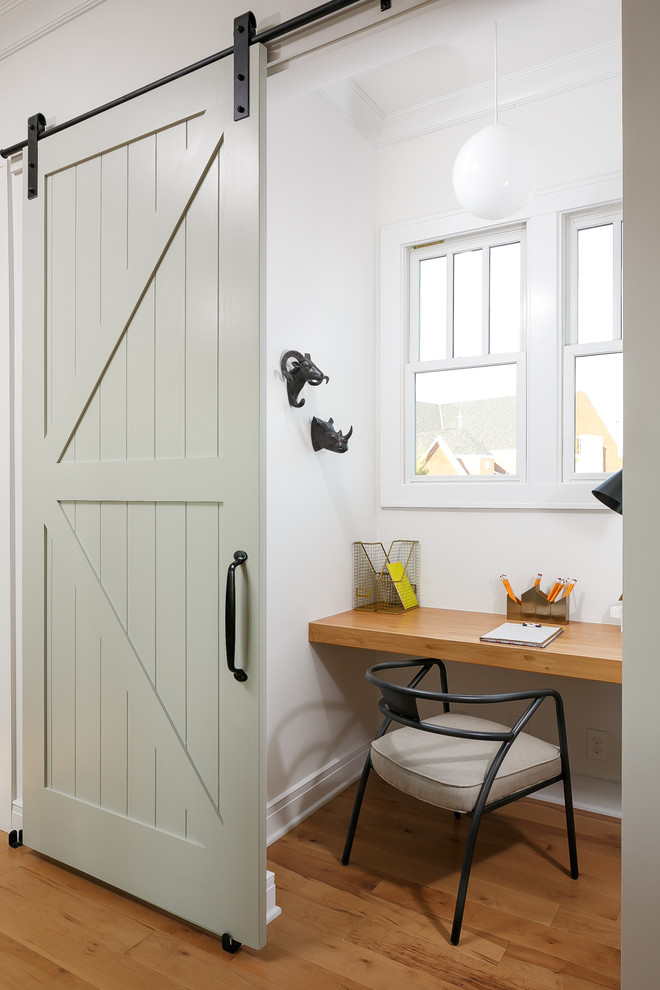 Inspiration for a small farmhouse built-in desk medium tone wood floor study room remodel in Louisville with white walls