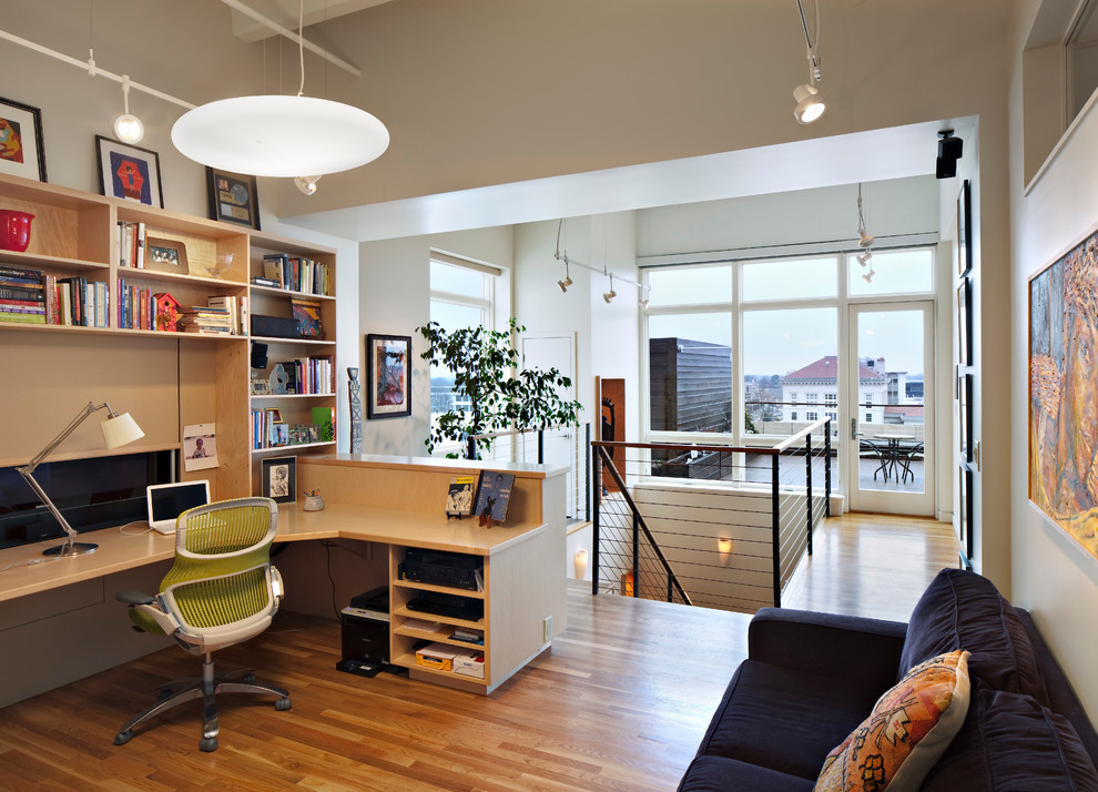 Example of a trendy built-in desk medium tone wood floor home office design in Raleigh with white walls