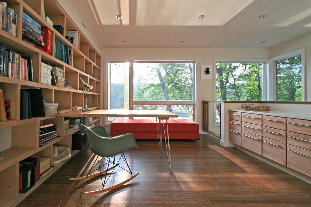 Example of a minimalist built-in desk dark wood floor home office design in New York with beige walls