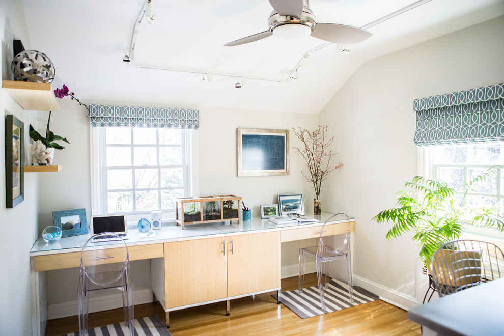 Example of a transitional built-in desk light wood floor study room design in New York with white walls