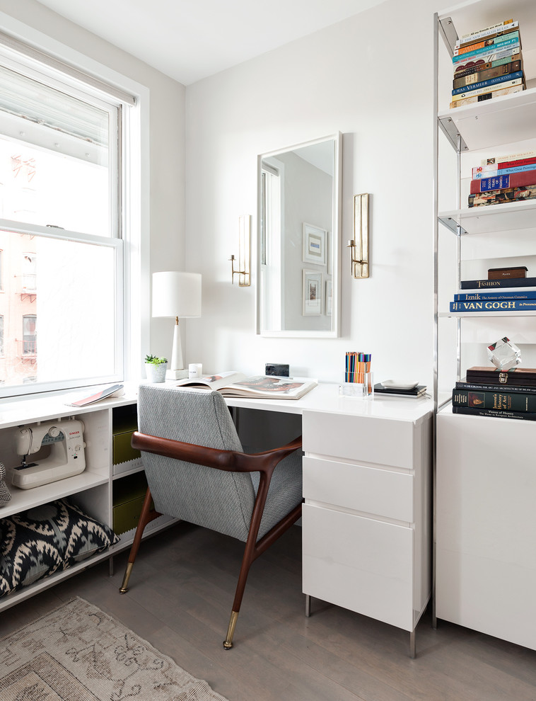 Trendy built-in desk light wood floor craft room photo in New York with gray walls