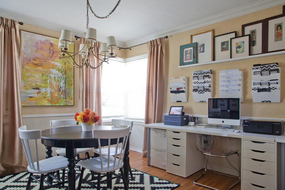 Example of a mid-sized classic built-in desk medium tone wood floor home office design in Los Angeles with yellow walls and no fireplace
