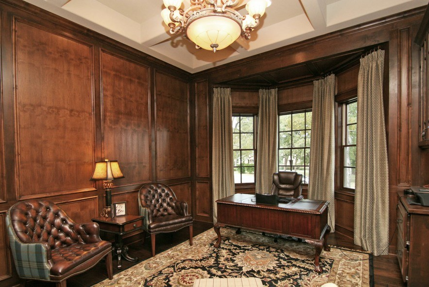 Study room - large traditional freestanding desk dark wood floor and brown floor study room idea in Austin with brown walls, a standard fireplace and a stone fireplace
