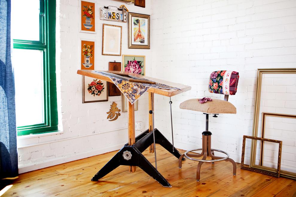 Example of an eclectic freestanding desk medium tone wood floor home studio design in Denver with white walls
