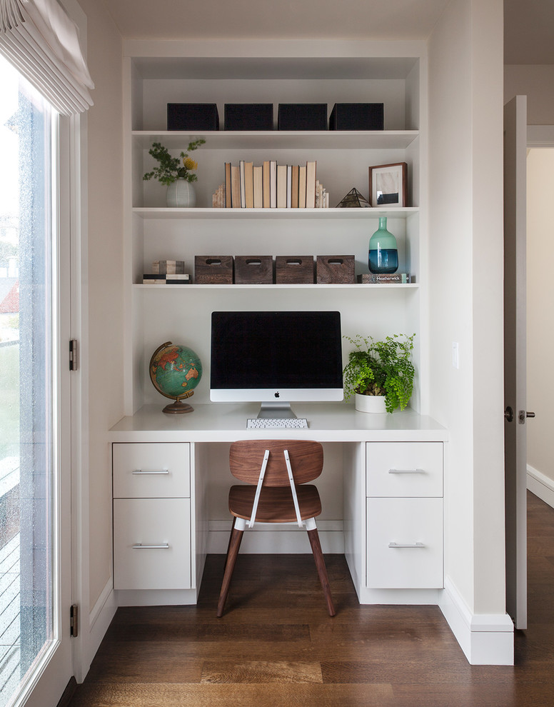 Trendy built-in desk dark wood floor study room photo in San Francisco with white walls