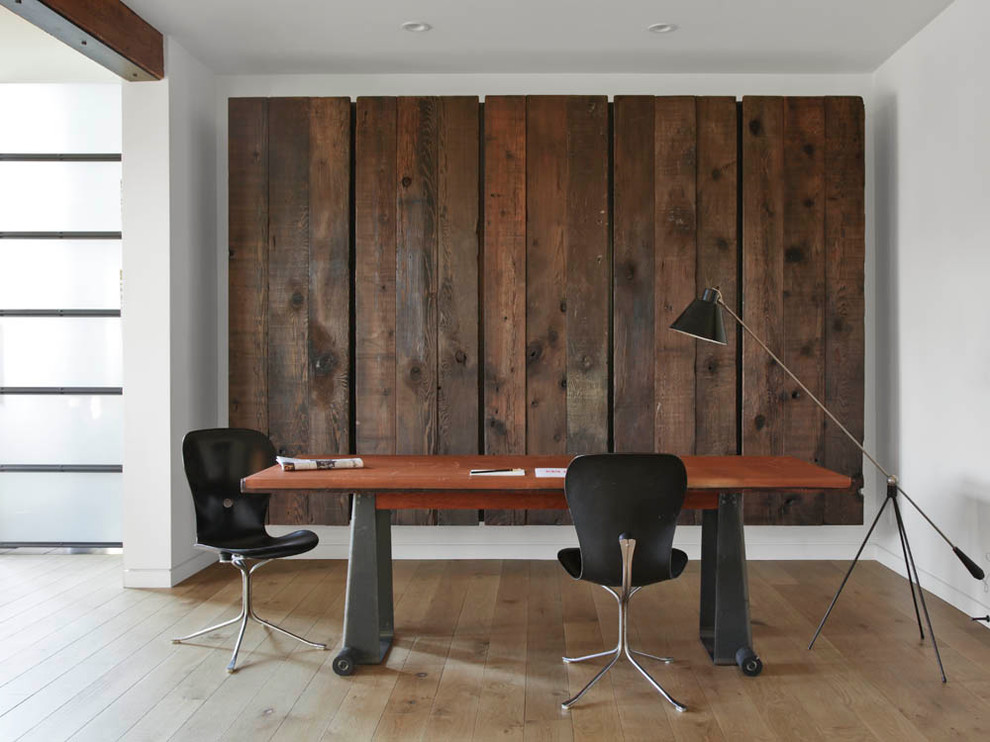 Trendy freestanding desk medium tone wood floor home office photo in San Francisco with white walls