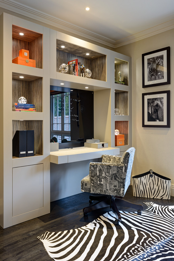 Home office - mid-sized transitional built-in desk dark wood floor and black floor home office idea in Surrey with beige walls