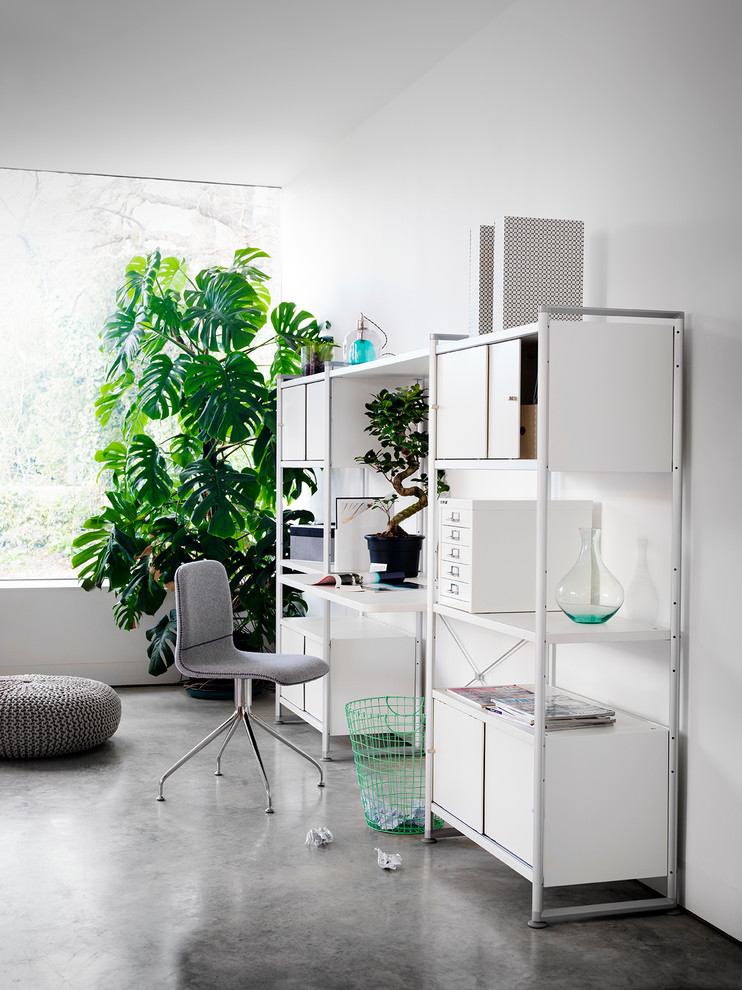 Home office - scandinavian freestanding desk concrete floor home office idea in London with white walls