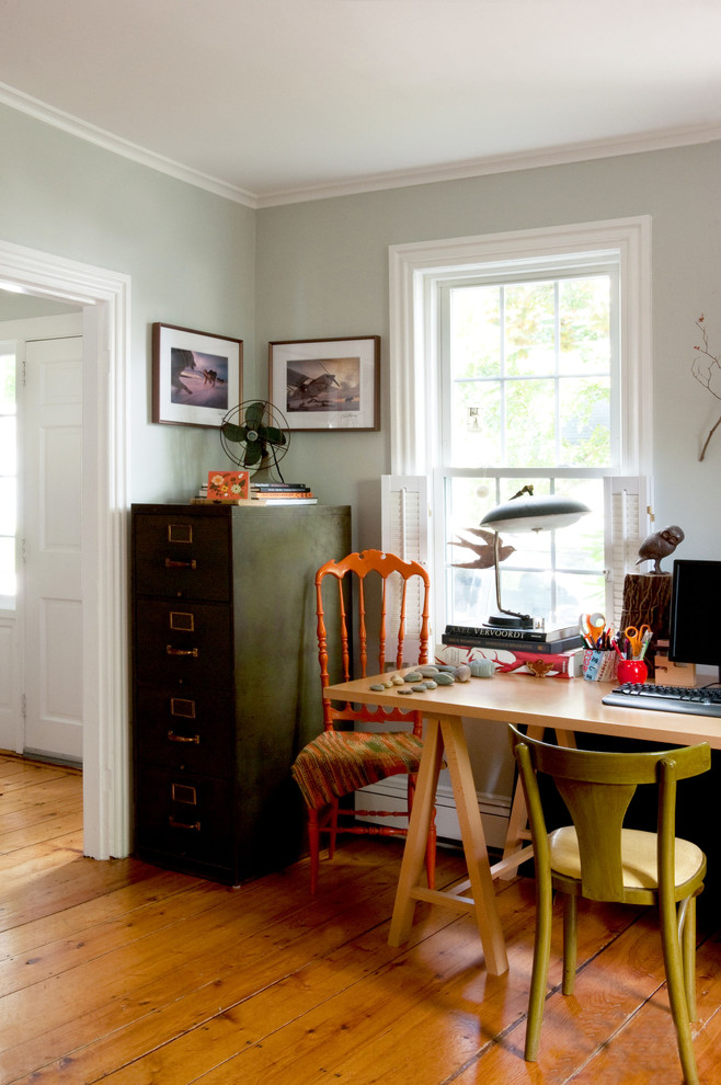 Example of an eclectic freestanding desk medium tone wood floor home office design in Boston with gray walls