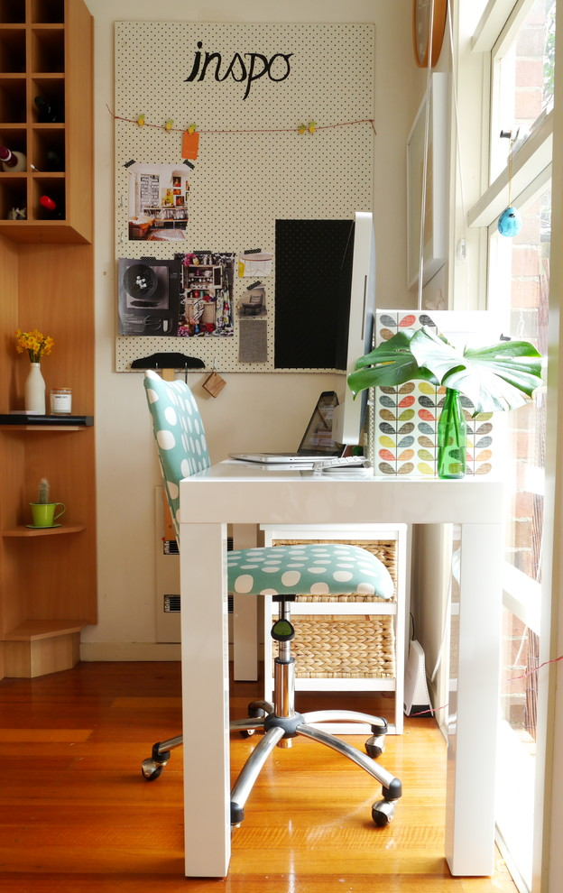 Example of an eclectic freestanding desk medium tone wood floor study room design in Melbourne with white walls