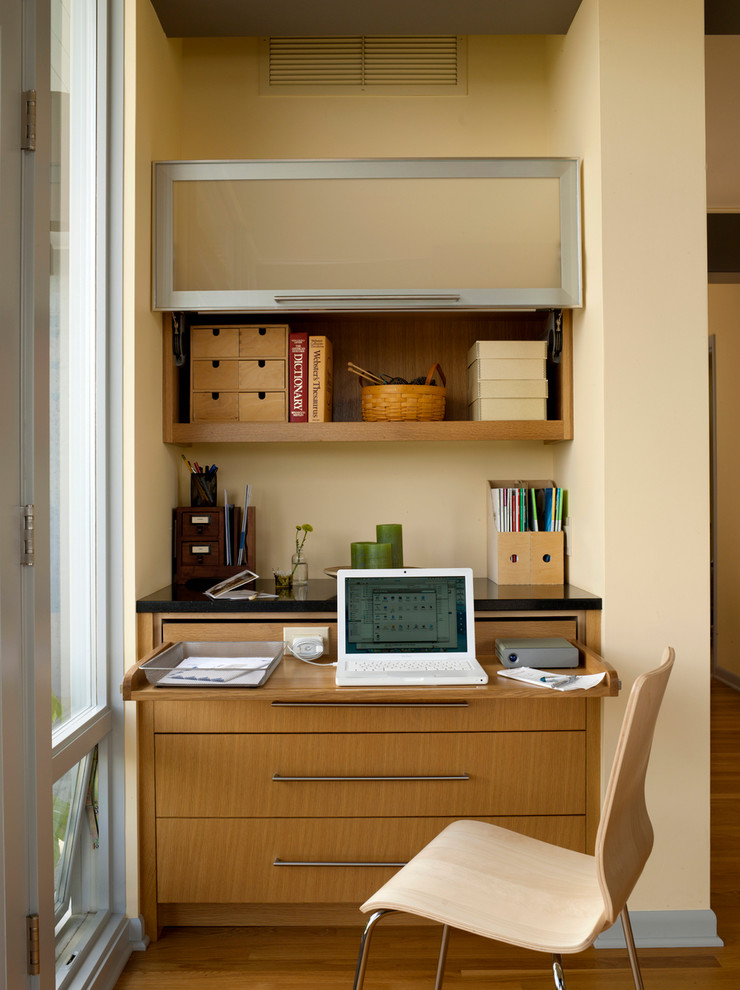 Mid-sized mid-century modern built-in desk medium tone wood floor home office photo in Seattle with beige walls and no fireplace