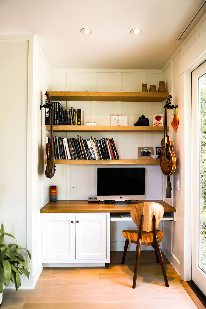 Example of a transitional built-in desk medium tone wood floor and brown floor home office design in San Francisco with white walls