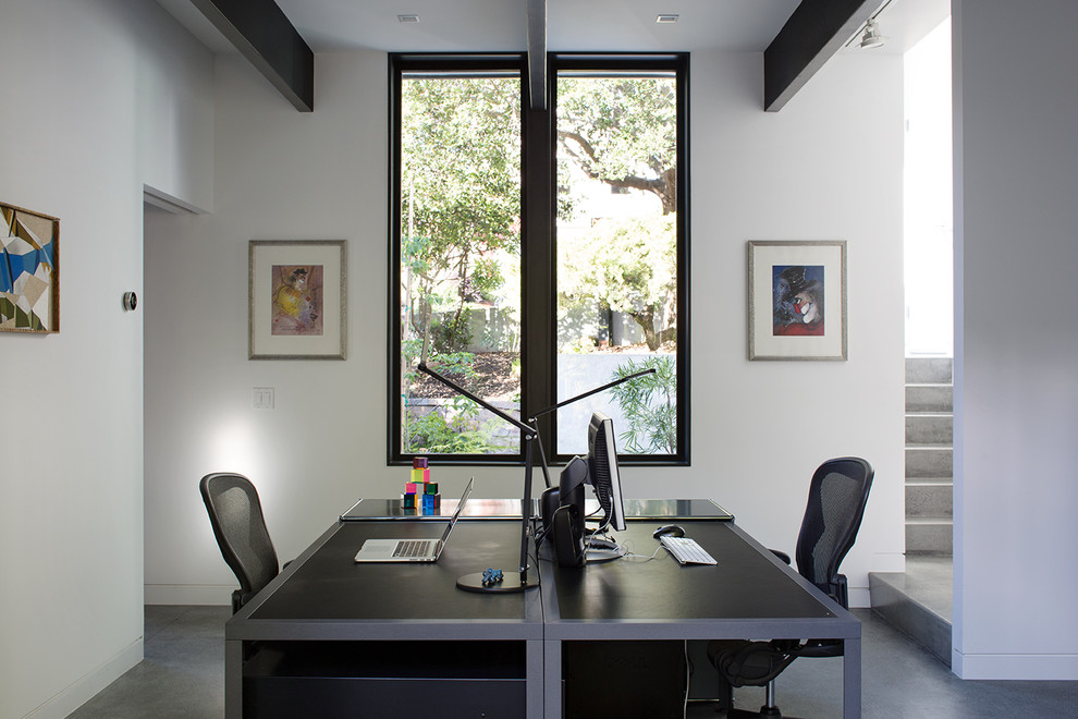 Example of a beach style freestanding desk concrete floor study room design in San Francisco with white walls