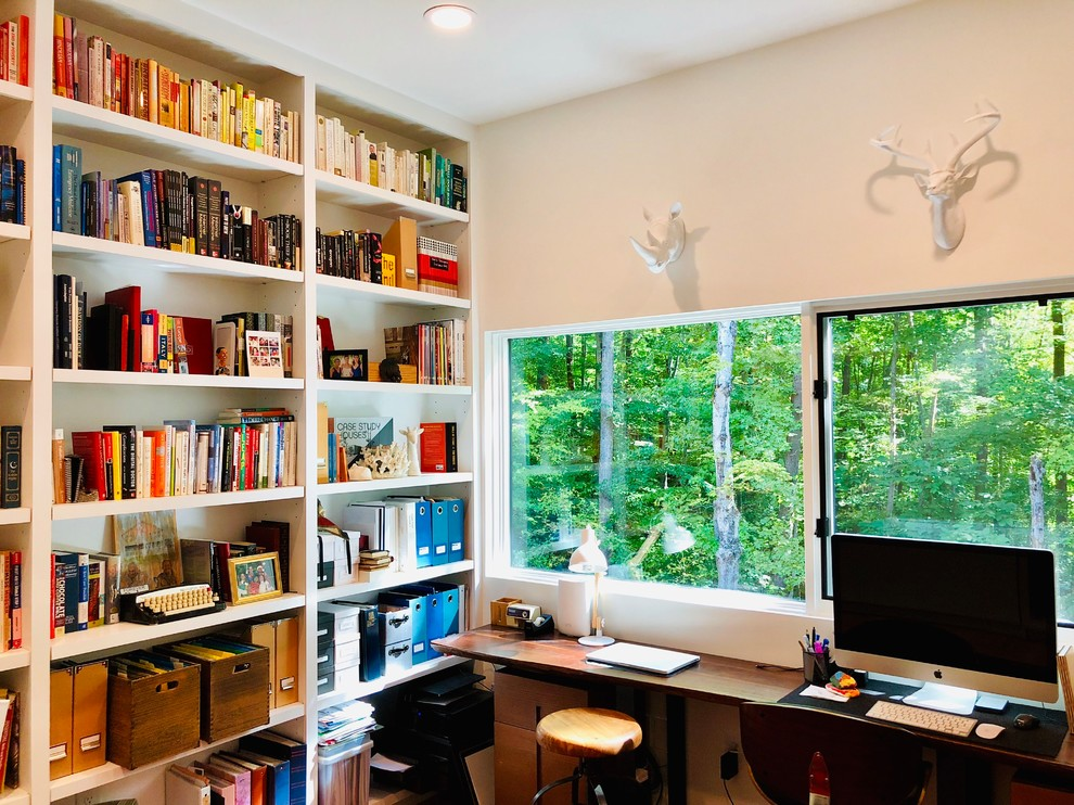 Inspiration for a contemporary freestanding desk home office library remodel in Raleigh with white walls