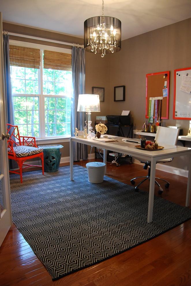 Example of a trendy freestanding desk dark wood floor home office design in Raleigh with brown walls