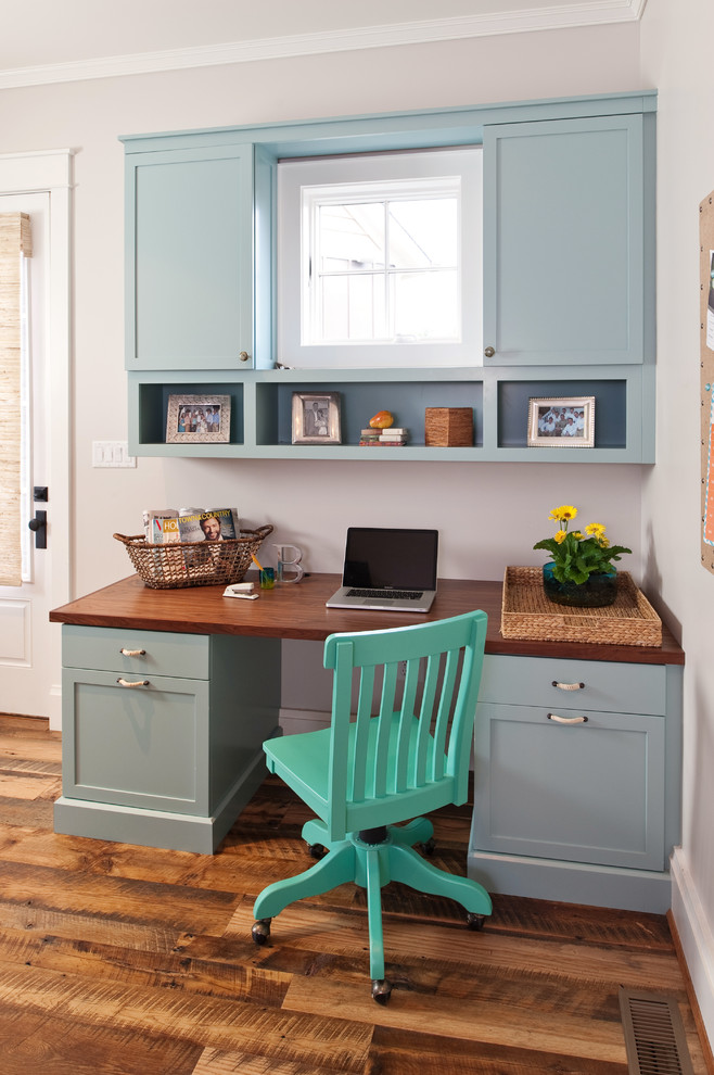 Example of a mid-sized mountain style built-in desk medium tone wood floor home office design in Richmond with gray walls and no fireplace