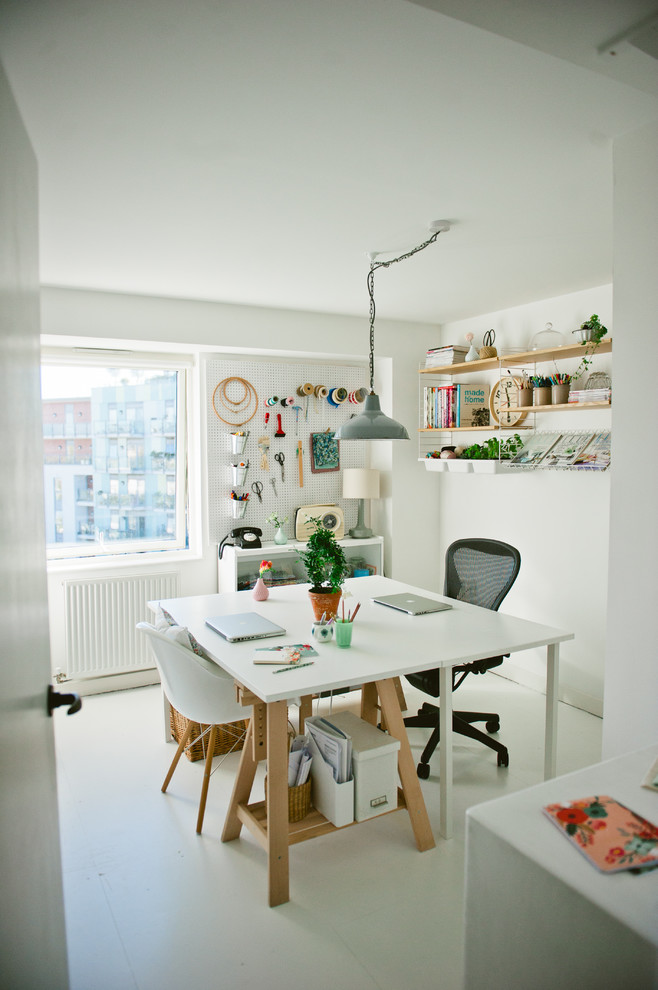 Example of a danish freestanding desk painted wood floor craft room design in London with white walls