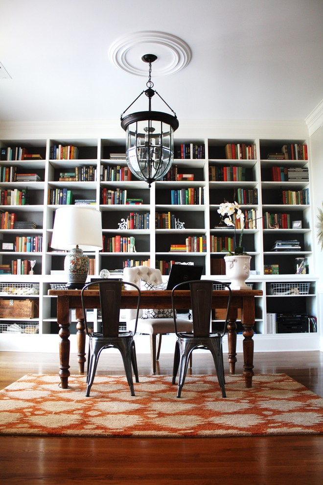 Example of an eclectic freestanding desk dark wood floor home office design in Charlotte with white walls