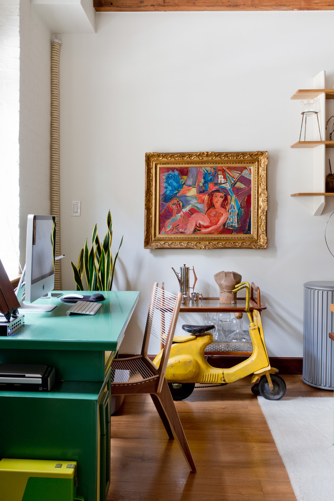 Inspiration for an eclectic freestanding desk medium tone wood floor home office remodel in New York with white walls