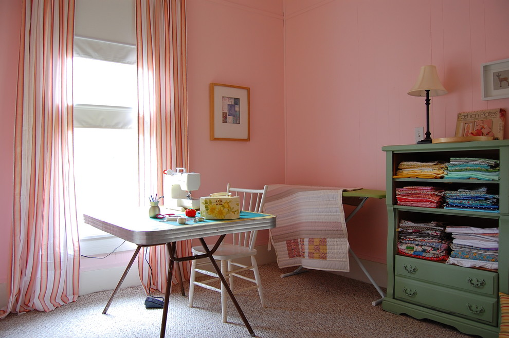 Example of a cottage chic home office design in New York with pink walls