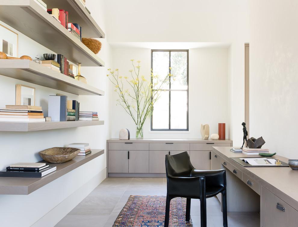 Imagen de despacho campestre con paredes blancas, escritorio empotrado y suelo gris