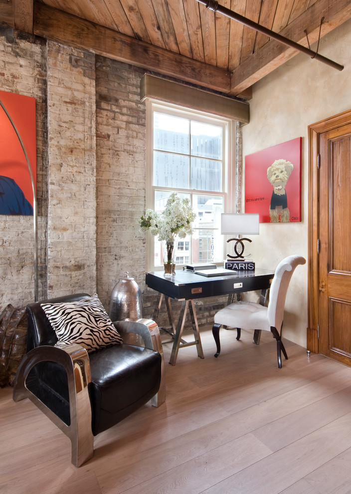 Example of an urban freestanding desk light wood floor and beige floor home office design in New Orleans with beige walls