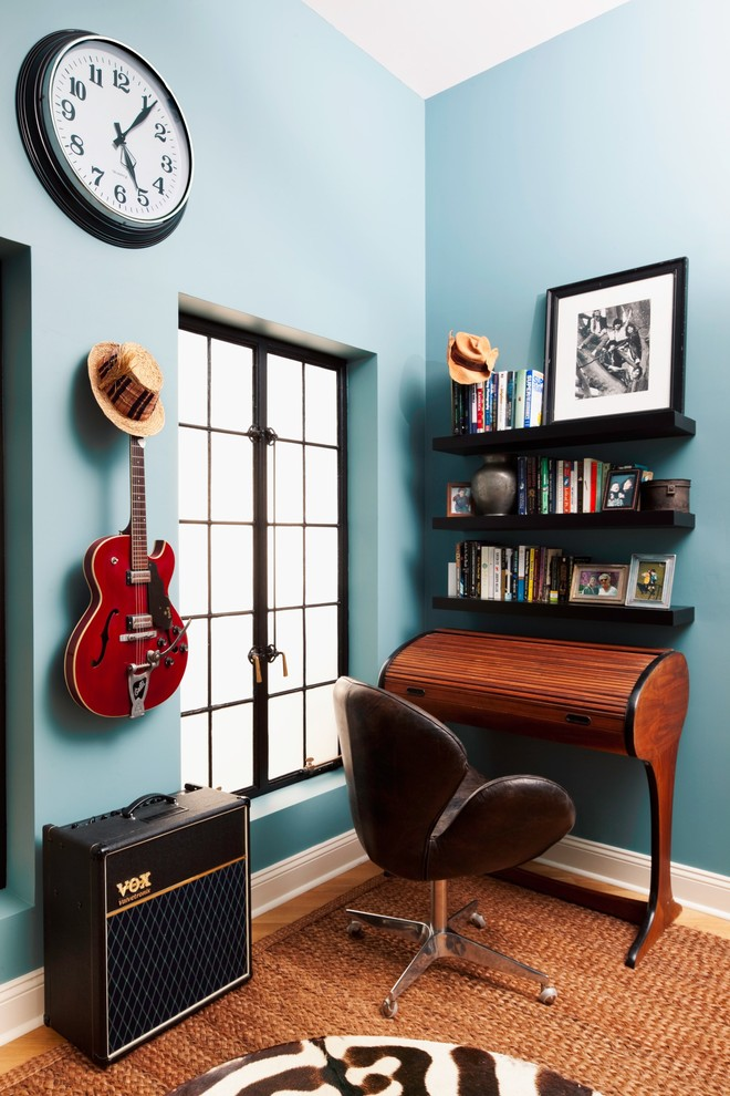 Example of an eclectic freestanding desk home office design in New York with blue walls