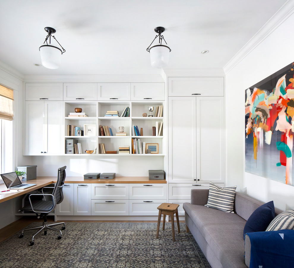 Mid-sized beach style built-in desk medium tone wood floor study room photo in Vancouver with white walls and no fireplace