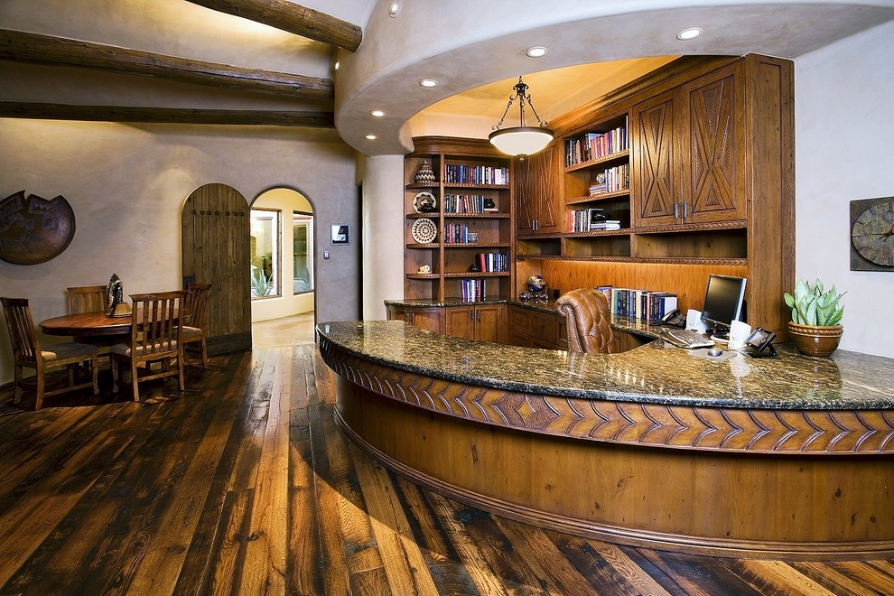 Study room - huge southwestern built-in desk dark wood floor and brown floor study room idea in Phoenix with white walls and no fireplace