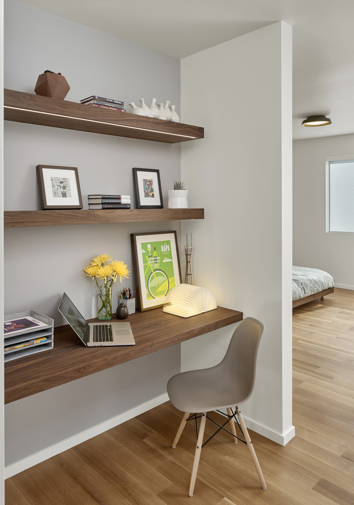 Inspiration for a small 1950s built-in desk light wood floor study room remodel in San Francisco with white walls