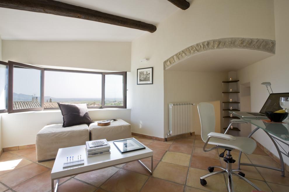 Home office - mediterranean freestanding desk terra-cotta tile home office idea in Marseille with white walls