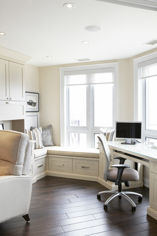 Inspiration for a timeless built-in desk dark wood floor home office remodel in Toronto with beige walls