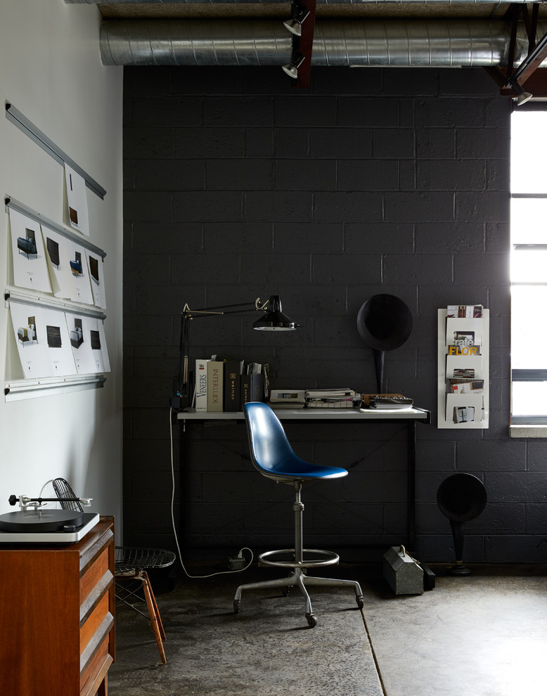 Urban freestanding desk concrete floor and gray floor home office photo in New York with black walls