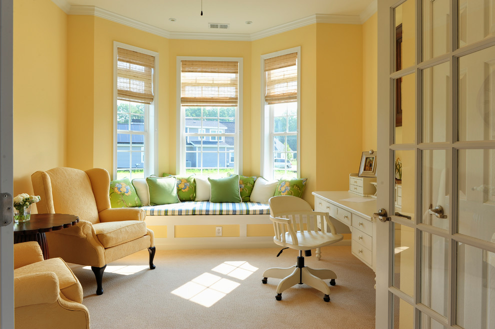Example of a classic freestanding desk carpeted home office design in Other with yellow walls