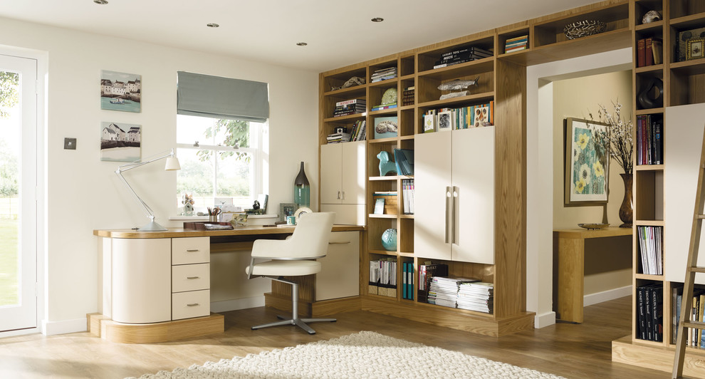 Inspiration for a large modern built-in desk brown floor study room remodel in Manchester with white walls
