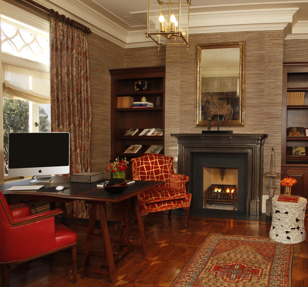 Example of a classic freestanding desk dark wood floor home office design in San Francisco with brown walls and a standard fireplace