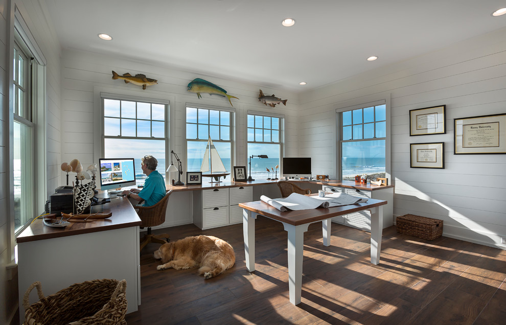 Example of a mid-sized coastal built-in desk dark wood floor and brown floor home studio design in Charleston with white walls