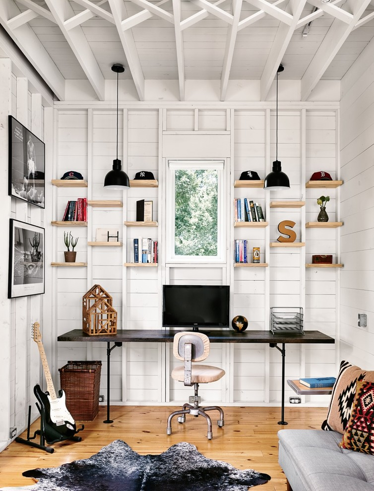 Mid-sized farmhouse built-in desk light wood floor study room photo in Austin with white walls