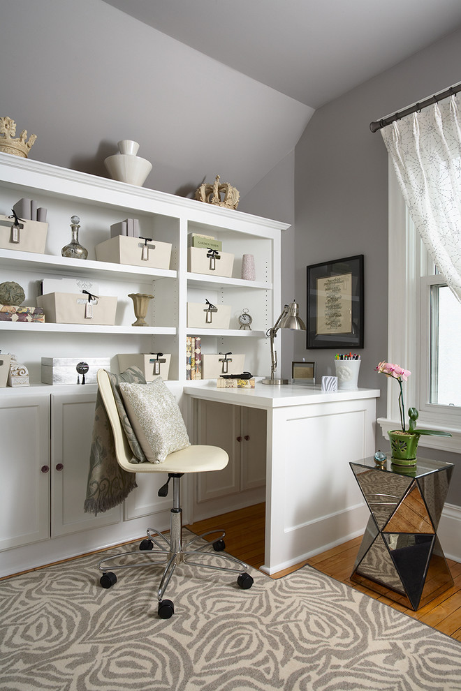 Example of a classic built-in desk medium tone wood floor home office design in Minneapolis with gray walls and no fireplace