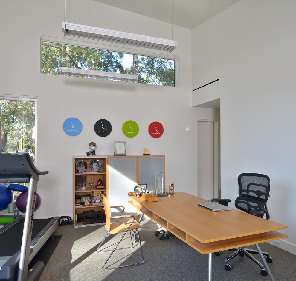 Minimalist freestanding desk carpeted home office photo in Houston with white walls