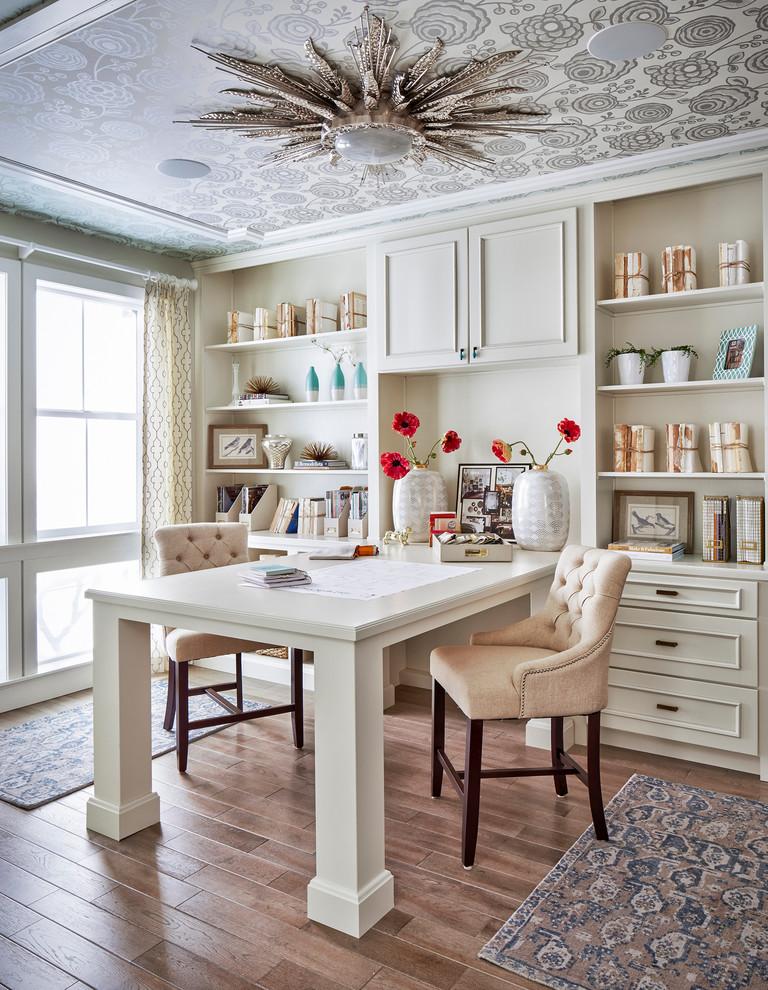 Example of a classic built-in desk medium tone wood floor home office design in Denver