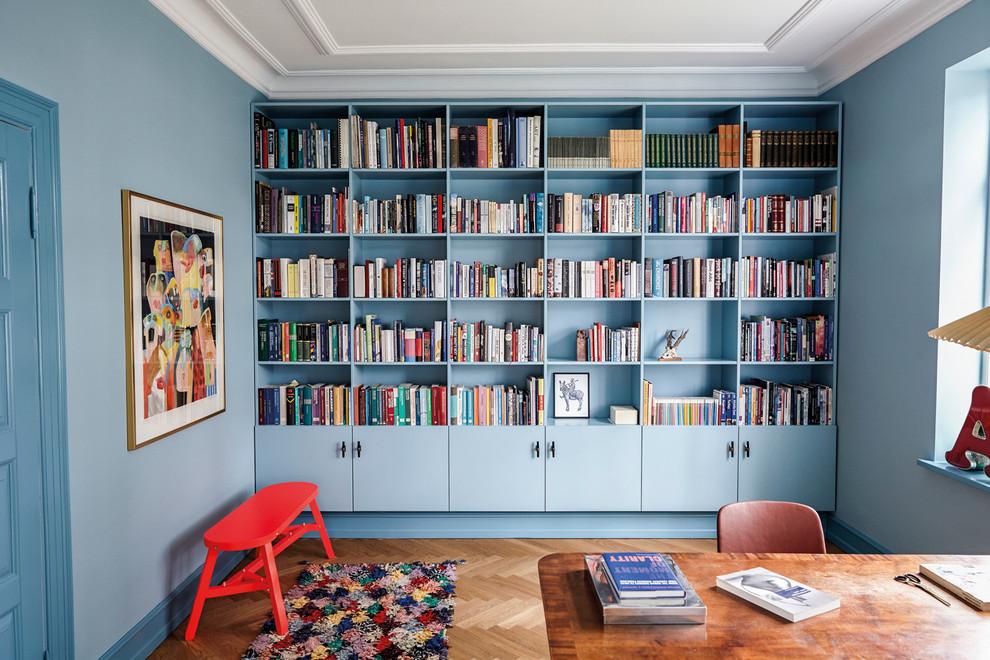 Study room - large mid-century modern freestanding desk medium tone wood floor study room idea in Copenhagen with blue walls and no fireplace