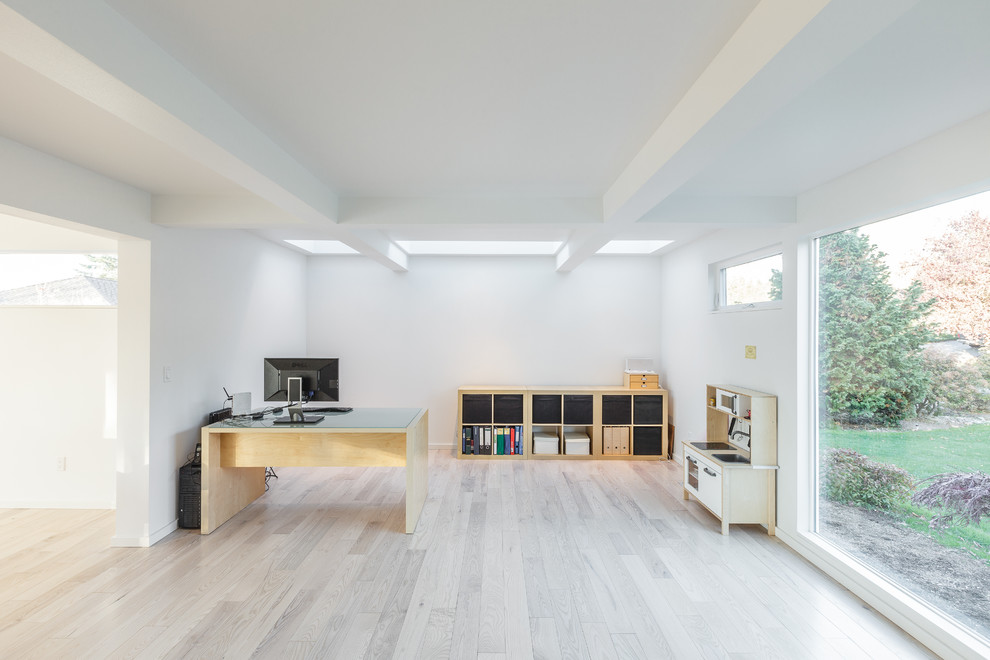 Inspiration for a large contemporary freestanding desk light wood floor study room remodel in Seattle with white walls