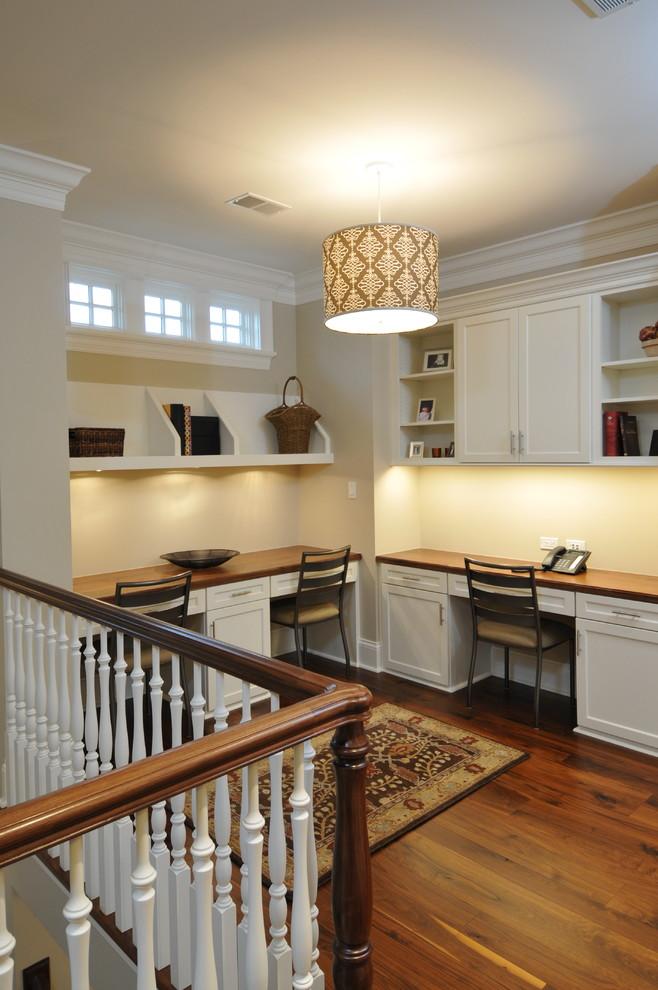 Elegant built-in desk dark wood floor home office photo in Chicago with beige walls