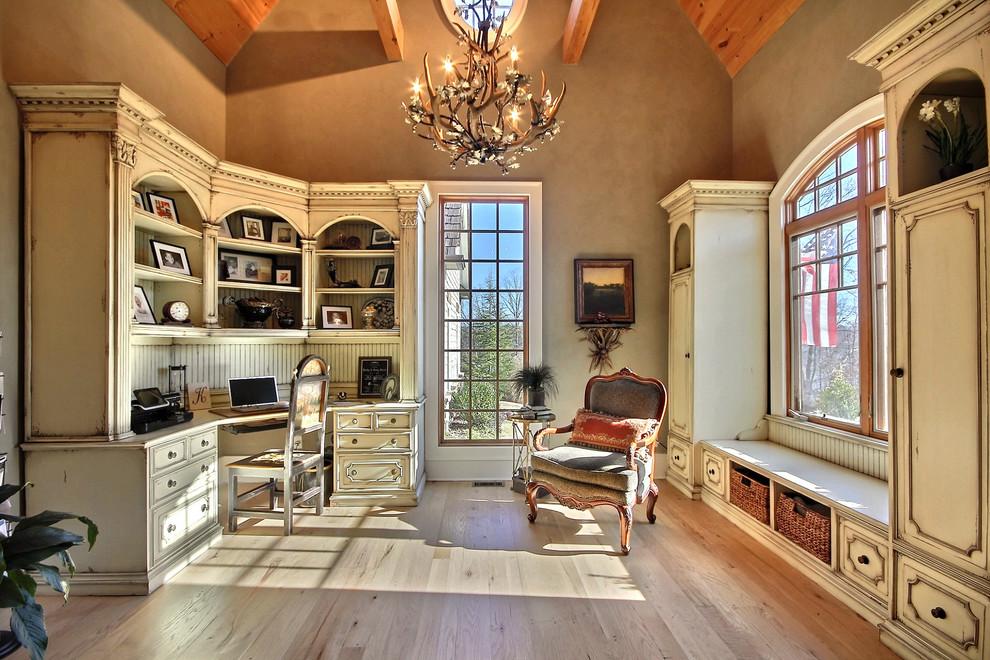 Example of a tuscan built-in desk medium tone wood floor home office design in Atlanta