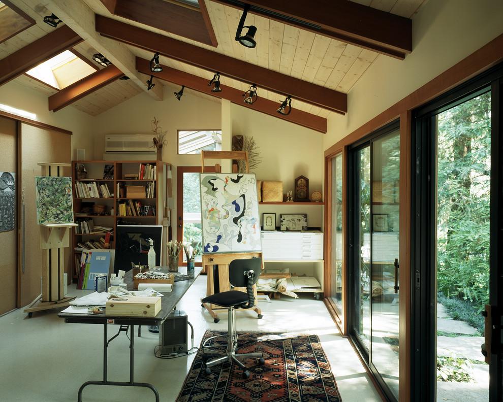 Trendy freestanding desk home studio photo in Los Angeles with beige walls