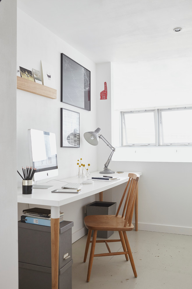 Example of a danish freestanding desk home office design in London with white walls and no fireplace